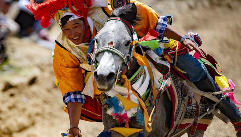 Dorf in Tibet feiert bevorstehende Erntezeit mit traditionellem Pferderennen